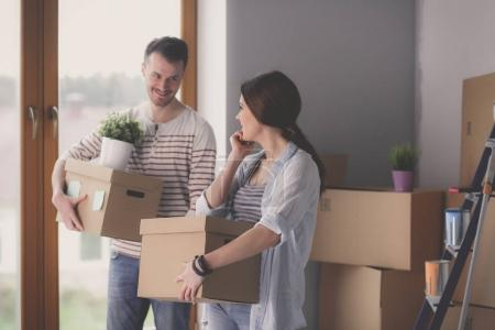 Photo for Happy young couple unpacking or packing boxes and moving into a new home. - Royalty Free Image