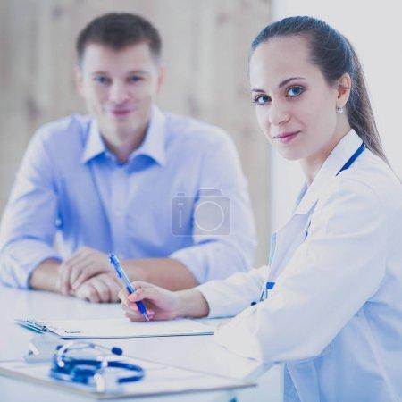 Photo pour Médecin femme assise avec un patient masculin au bureau . - image libre de droit