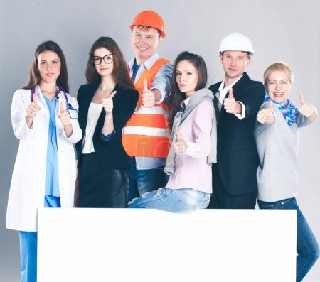 Photo for Happy group of people of different professions holding a blank billboard - Royalty Free Image