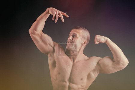 Photo for Muscular man bodybuilder training in gym and posing muscle - Royalty Free Image