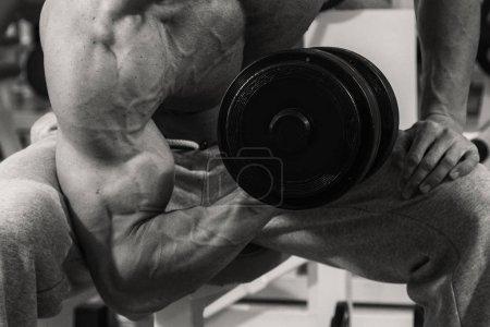 Photo pour Musclé homme bodybuilder formation dans la salle de gym et de poser le muscle - image libre de droit
