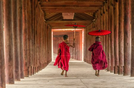 Back side of two young monk holding traditional um...