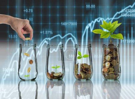 Photo pour Main mettant des pièces d'or et des semences en bouteille claire sur les données boursières sur fond d'affichage LED, Croissance de l'investissement des entreprises et concept de négociation - image libre de droit