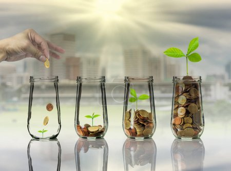 Photo for Hand putting Gold coins and seed in clear bottles on cityscape photo blurred cityscape background,Business investment growth concept - Royalty Free Image