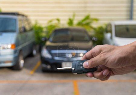 Photo pour Main tenant et touchant les clés sur la photo floue de voiture d'occasion pour ouvrir la voiture de porte, concept de transport et de propriété - image libre de droit