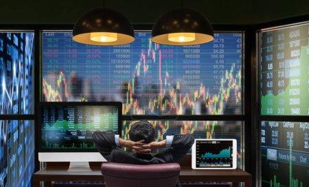 Photo pour Face arrière de l'homme d'affaires assis qui regarde le graphique de la bourse sur le paysage urbain sur le fond grand écran et ordinateur de bureau avec tablette montrant le graphique de trading, concept de commerce - image libre de droit