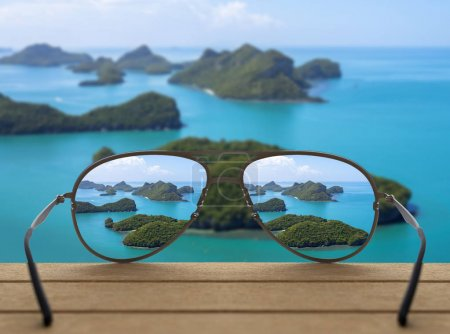 Photo for Conceptual image of landscape focused in glasses lenses over the photo blurred of Top view of Ang Thong National Marine Park with rainbow, Thailand - Royalty Free Image