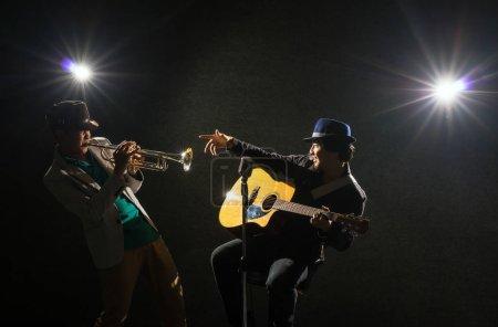 Photo pour Bande de Duo de musicien jouant de la trompette et un chant et jouer de la guitare sur fond noir avec spot de lumière et la lumière parasite, concept musical - image libre de droit