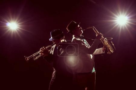 Photo pour Musicien Duo band jouer de la trompette avec spot light et lentille fusée éclairante sur scène, concept musical - image libre de droit