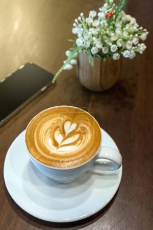 Photo pour Tasses à café sur la table avec faux décorent fausses fleurs et téléphone mobile dans la boutique de café, vue de dessus, le concept de boisson - image libre de droit