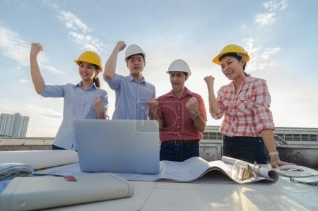 group of professional engineers with blueprints