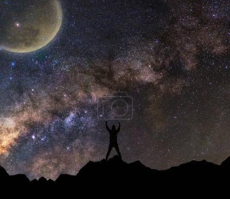 Foto de Silueta del hombre con los brazos levantados a la luna con el fondo de la vía Láctea, elementos de esta imagen proporcionada por la Nasa - Imagen libre de derechos