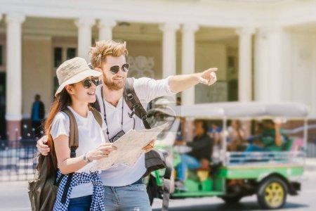 Photo pour Voyageurs multiethniques sont à la recherche de la destination et tenant la carte à la gare, Voyage et concept de transport - image libre de droit