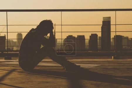 depressed man on rooftop