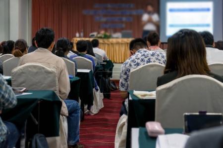 Foto de Vista posterior de audiencia borrosa con altavoces en el escenario en la Conferencia pasillo o seminario de encuentro, negocios y educación concepto - Imagen libre de derechos
