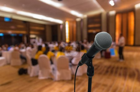 Microphone over blurred conference hall interior