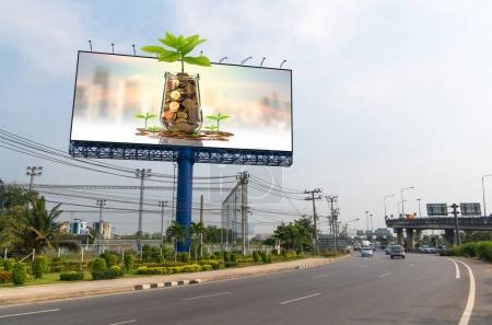 Photo pour Panneau d'affichage avec des pièces d'or en pot de verre sur fond de paysage urbain floue, concept de croissance investissement commercial - image libre de droit