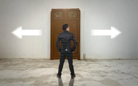 Businessman standing in front of wooden door