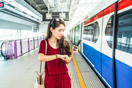 Asian woman passenger watching clock
