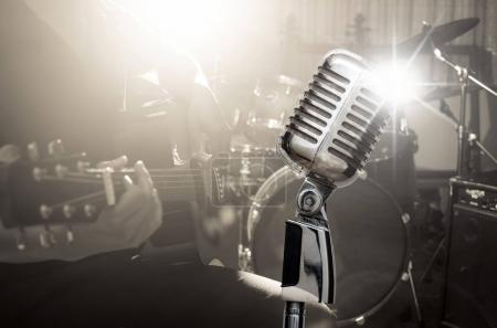 Photo for Retro microphone over the musician playing the guitar on band background with spot light, musical concept - Royalty Free Image