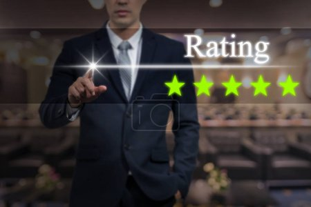 Businessman pointing five star rating