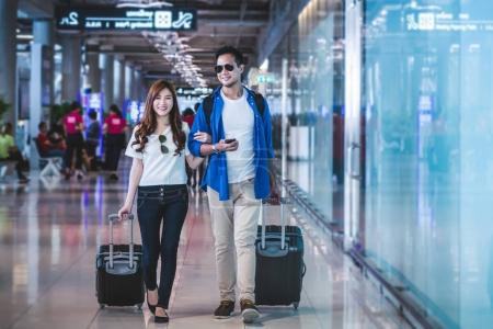 Asian couple of travelers walking with suitcases