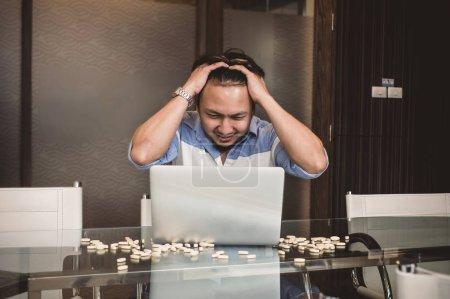 Desperate asian businessman at laptop