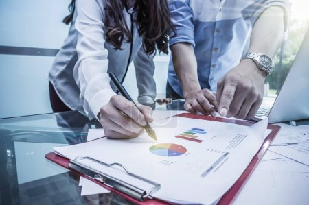 Photo for Business documents with laptop on the workplace with group of business teamwork working blurred background in the office meeting room - Royalty Free Image