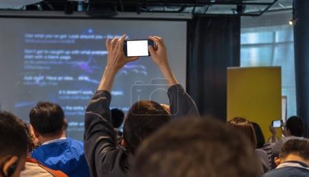 Photo pour Closeup certains participant compte de la présentation de la photo en fond de salle hall ou séminaire conférence - image libre de droit