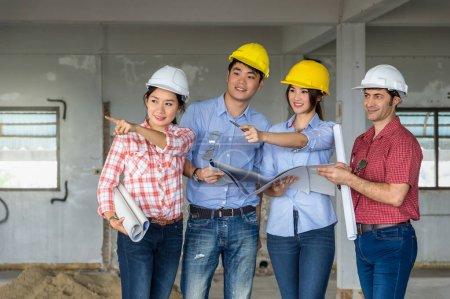 Photo pour Groupe d'ingénieurs professionnels avec des plans de travail sur le chantier, Industriel et travail d'équipe Concept - image libre de droit