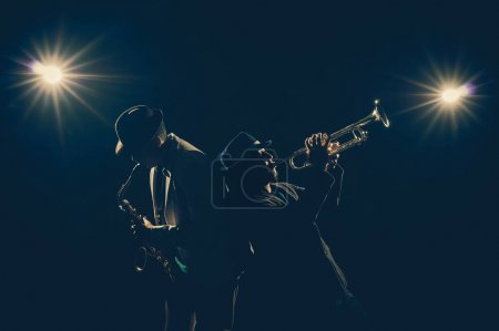 Photo for Musician Duo band playing a Trumpet and keyboard on black background with spot light and lens flare, musical concept - Royalty Free Image