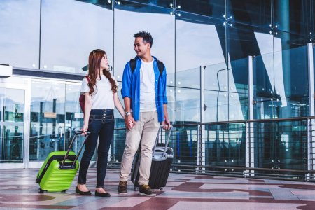 Asian couple travelers with suitcases at the airport. Lover travel and transportation with technology concept.