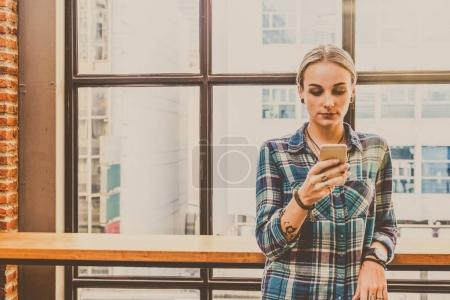 Hipster young Woman freelancer using smart phone mobile for working in the Loft cafe workplace. Creative Startup and entrepreneur business concept