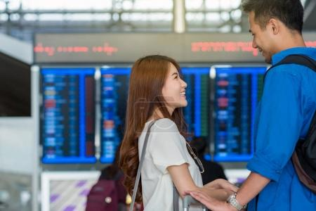 Asian couple traveler checking the flight with excited feeling at the travel information screen in modern an airport, travel and transportation concept.