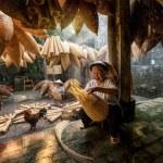 Old Vietnamese female craftsman making the traditi...