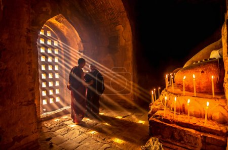 Two asian Burmish monks change the robe with sun ray in pagoda at bagan, mandalay, myanmar
