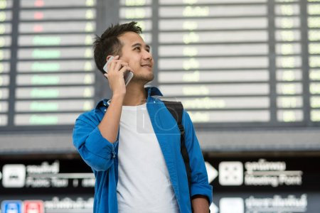Asian traveler using the smart mobile phone and calling for check-in at the flight information screen in modern an airport