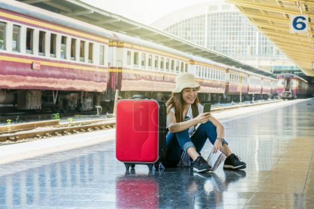 Asia woman Traveller sitting and looking at the smart mobile phone before go to travel at the train station, Travel and lifestyle concept