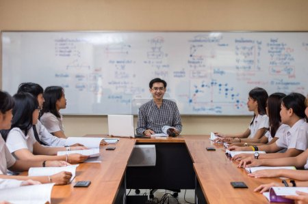 Asian teacher Giving Lesson to group of College Students in the classroom, University education concept