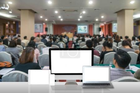 Computer set show on the white table over the Abstract blurred photo of conference hall or seminar room with attendee background, business technology and education concept