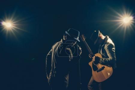 Photo pour Musicien Duo main du groupe tenant le microphone et chantant une chanson et jouant de la guitare sur fond noir avec projecteur et fusée éclairante, concept musical - image libre de droit