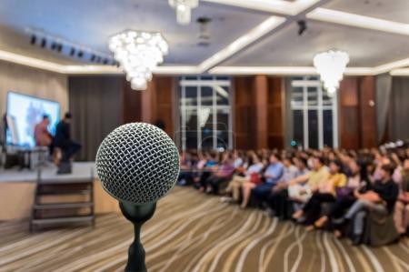Photo pour Microphone sur le résumé floue la photo de la salle de conférence salle ou séminaire avec fond de participant, le concept de réunion d'affaires - image libre de droit