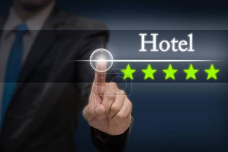 Businessman pointing five star button to increase rating of hotel on dark blue tone background, business evaluation concept, Increase rating