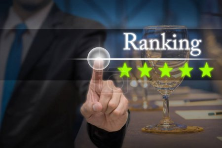 Businessman pointing five star button to increase ranking of hotel over workplace with Glass of water, paper and pencil on the table in the hall room, business evaluation concept, Increase rating