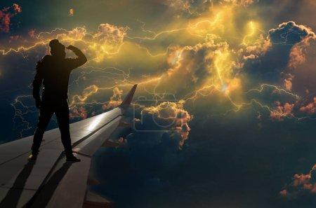Foto de Silueta de hombre mirando relámpagos truenos nubes y tormenta en el ala del aeroplano, concepto de negocio de desafío - Imagen libre de derechos