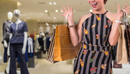 Happy woman shopping with happy feeling over the Abstract blurred photo of clothing store in a shopping mall department store, shopping concept
