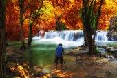 Photographer taking photo scene of Beautiful waterfall in the deep forest, huay mae khamin waterfall, Kanchanaburi province, thailand, Nature travel concept