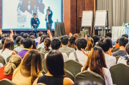 Orador en el escenario con vista posterior de la audiencia en la Conferencia pasillo o seminario de encuentro, negocios y educación concepto