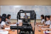 Professional digital camera on tripod recording video of Asian teacher in classroom, Camera for photographer and Technology Live Streaming concept, University education concept