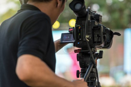 Rear side of Video Cameraman taking photograph to the stage, event and seminar production equipment concept